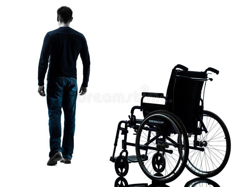 Человек идя далеко от силуэта кресло-коляскы стоковое фото
