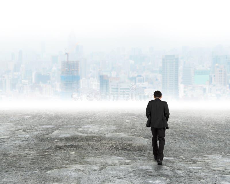 Человек идя к зданиям города в тумане стоковые фото
