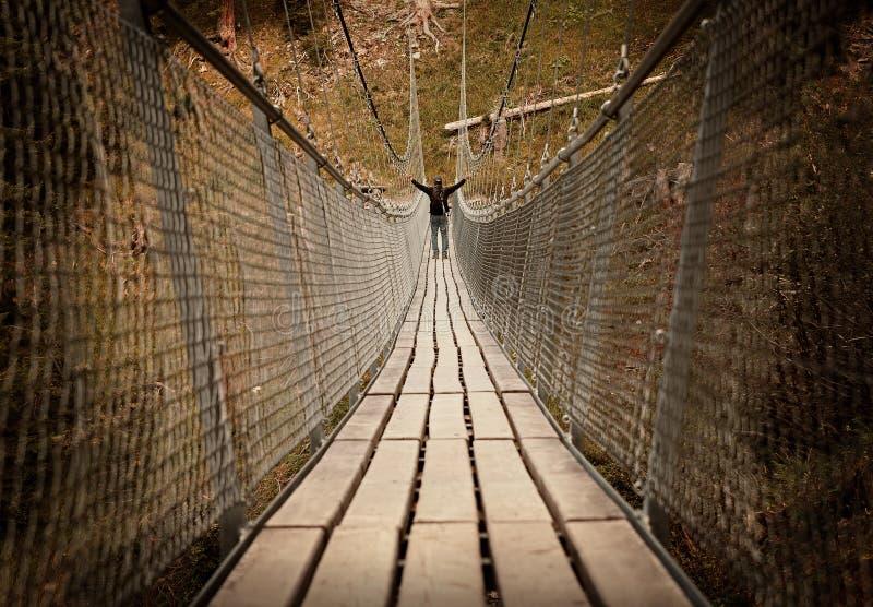 Человек идя над мостом веревочки стоковое фото