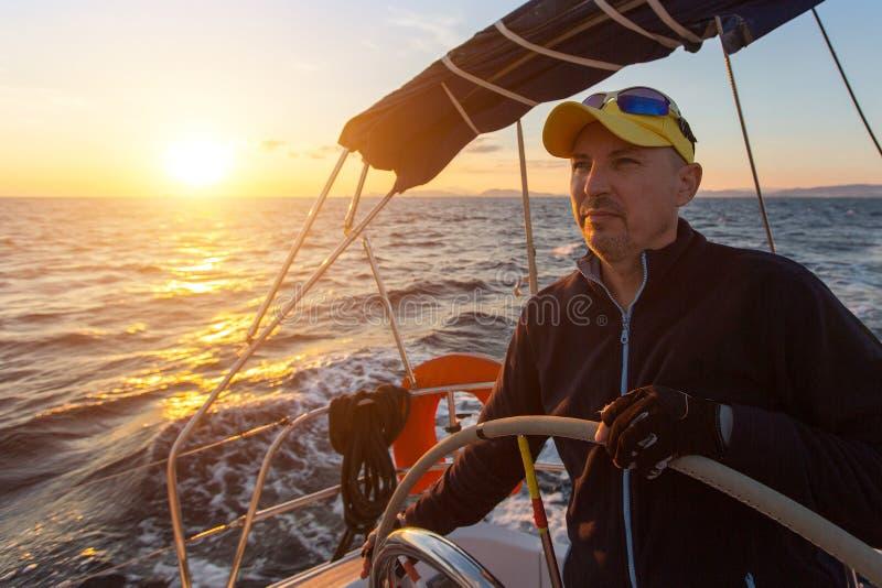 Человек контролирует парусное судно на заходе солнца стоковое фото rf