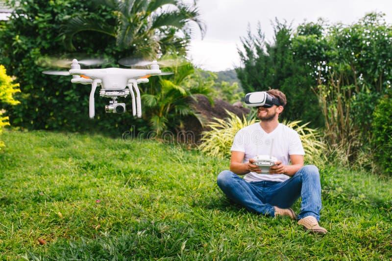 Человек контролирует quadrocopter стоковые изображения