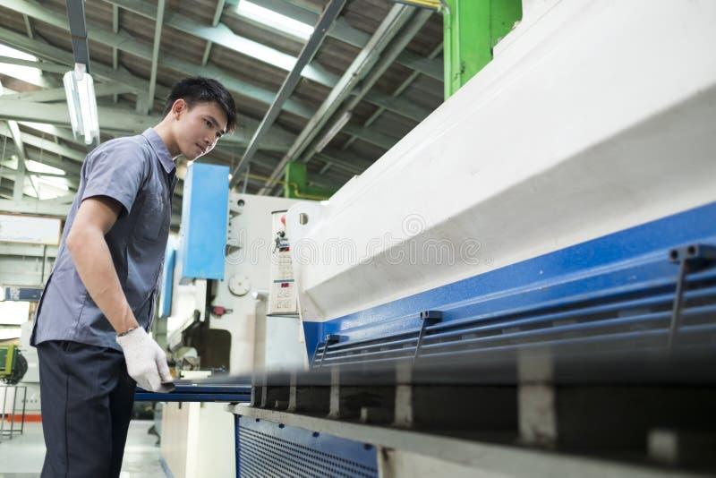 Человек контролируя машину гидравлической прессы стоковые фото