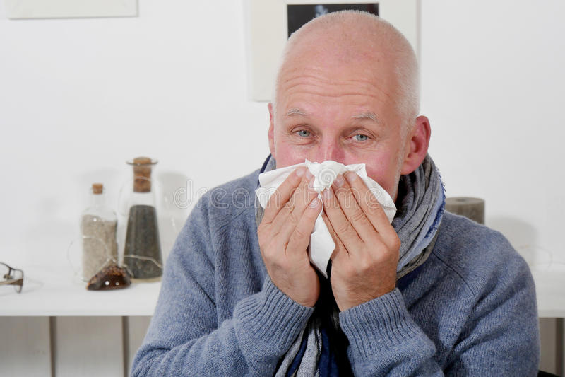 Человек который имеет грипп дует его нос стоковые изображения