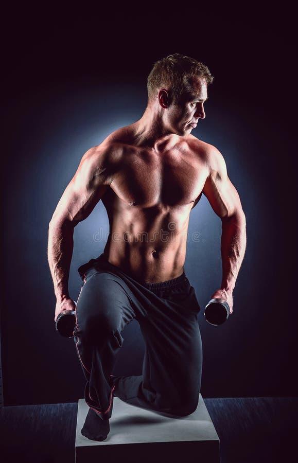Человек красивой силы атлетический в тренировке нагнетая вверх muscles с гантелями Гантель мышечного культуриста фитнеса поднимая стоковые фотографии rf