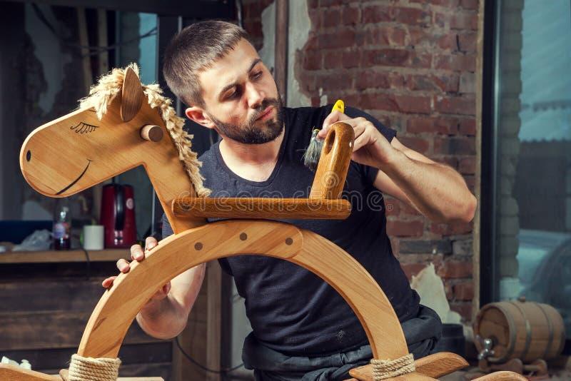 Человек красит деревянную игрушку стоковые фотографии rf