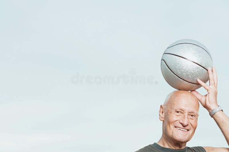 Человек кладя баскетбол на его голову стоковые фото