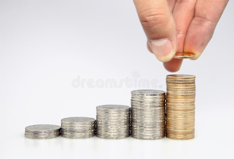 Человек кладя монетку к поднимая стогу монеток стоковая фотография