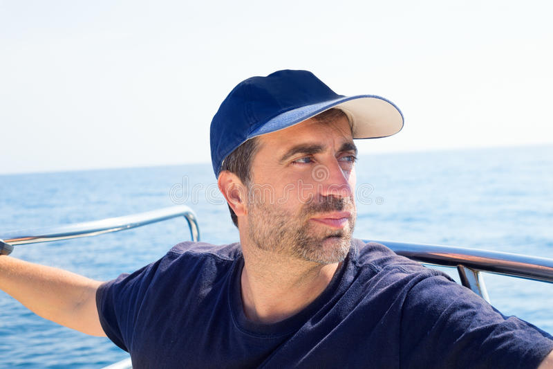 Человек матроса на смычке шлюпки при крышка смотря прочь море стоковые фотографии rf