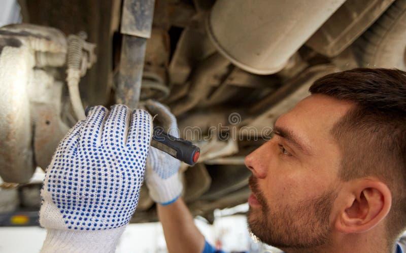 Человек механика при электрофонарь ремонтируя автомобиль на магазине стоковая фотография rf