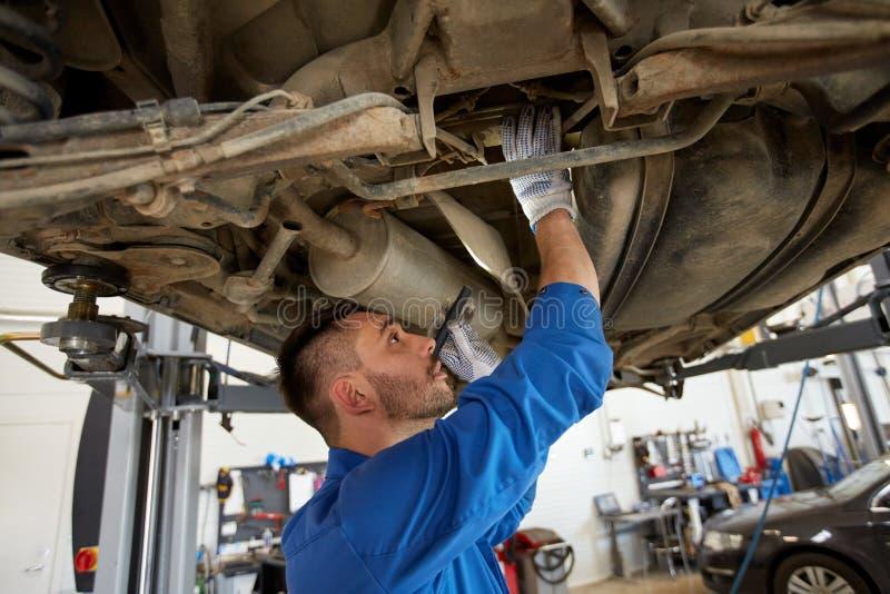 Человек механика при электрофонарь ремонтируя автомобиль на магазине стоковые изображения