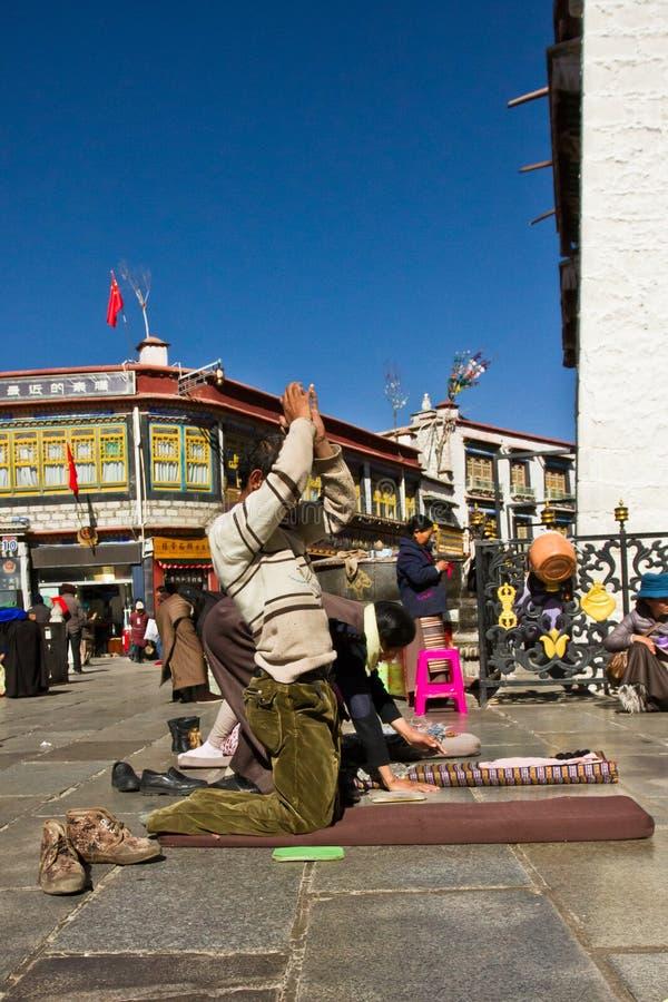 Человек молит к виску Jokhang в квадрате Barkhor, Лхасе Тибете стоковое изображение