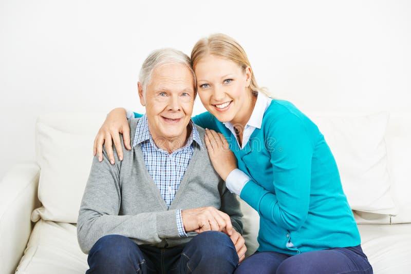 Человек молодой женщины обнимая старший стоковая фотография