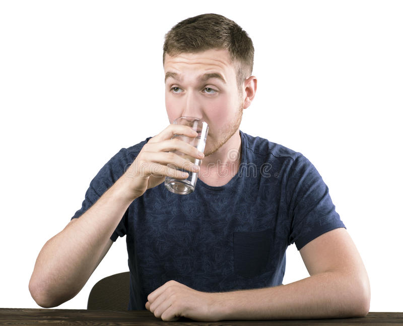 Человек молодости нет уверенно питьевой воды, изолированной на белой предпосылке Мальчик в голубой футболке принимает глоточек во стоковая фотография rf