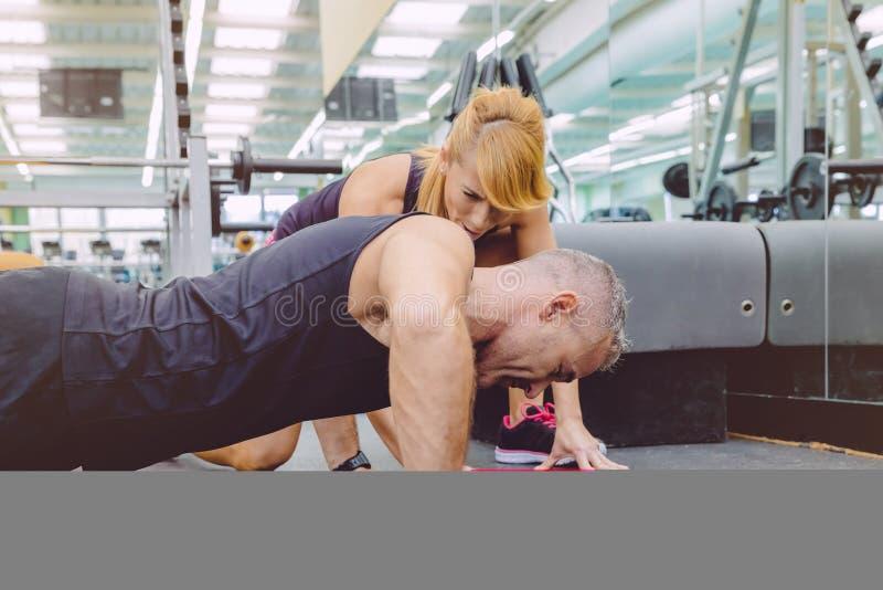 Человек мышцы личного тренера ободряющий в нажиме стоковые фотографии rf