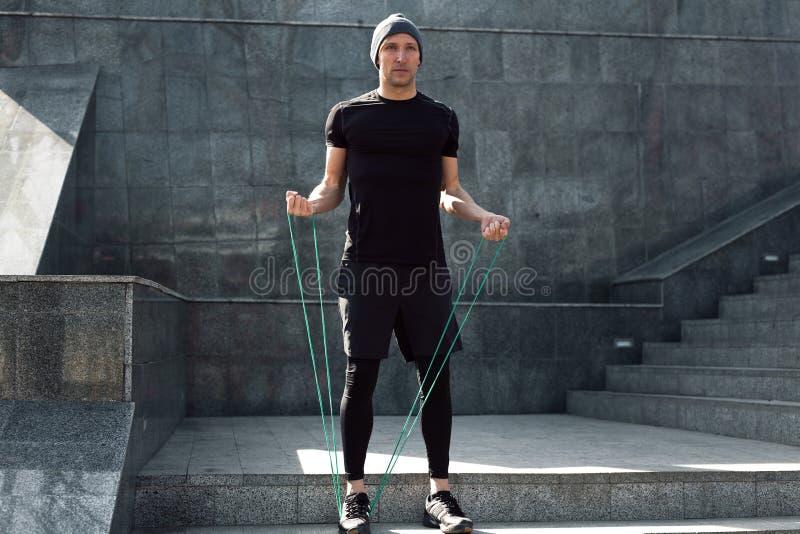 Человек нагревая с скача веревочкой стоковое фото
