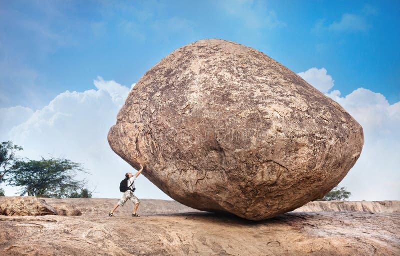 Человек нажимая большой камень стоковая фотография rf
