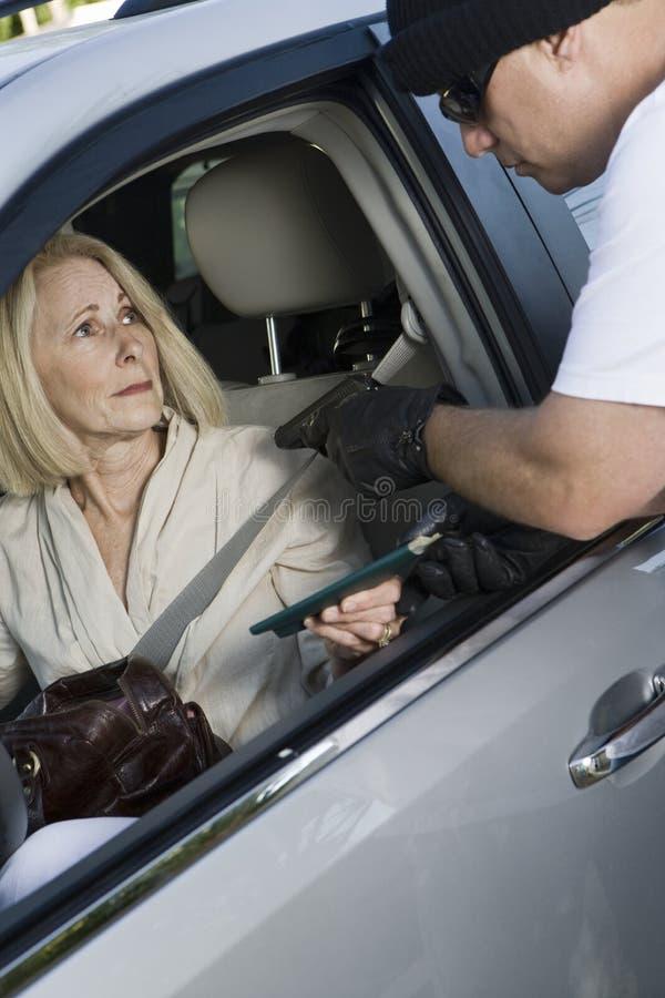 Человек нападает женщину с огнестрельным оружием через окно автомобиля стоковое фото rf