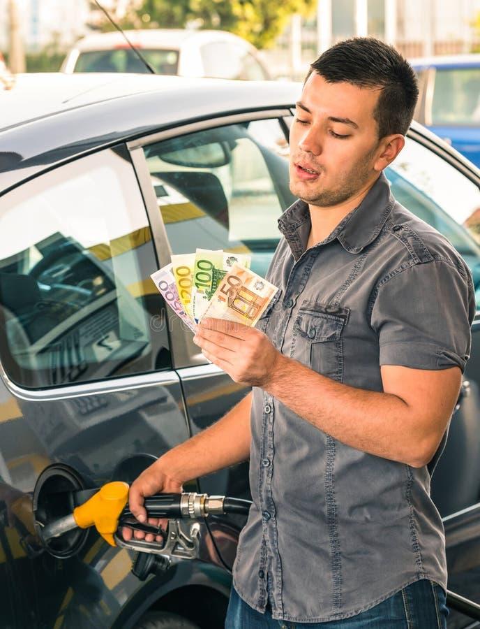 Человек на АЗС общаясь с деньгами для повышений цены стоковое изображение