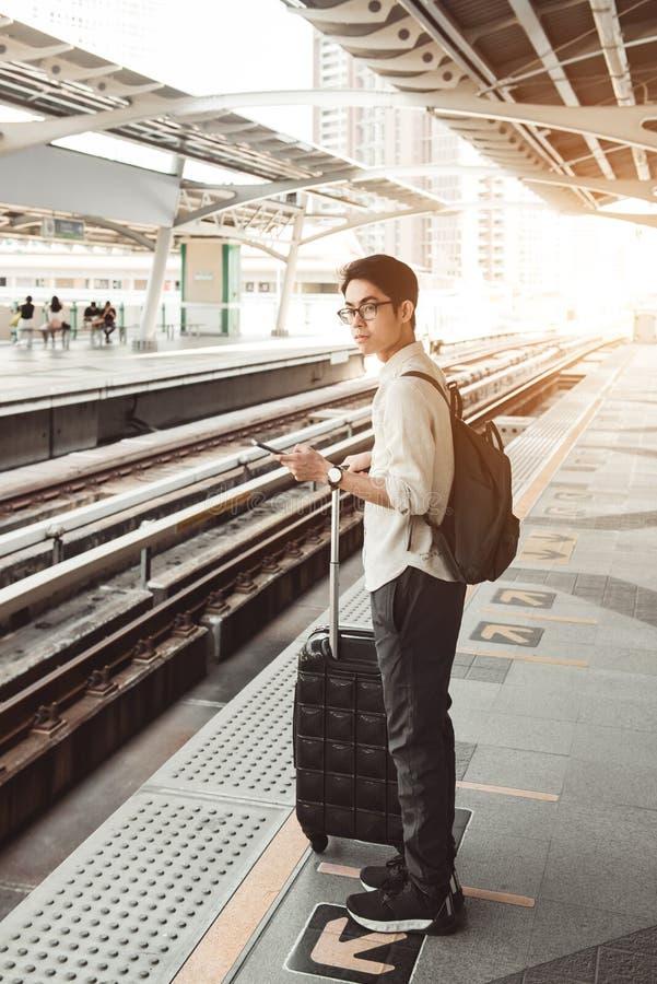 Человек на вокзале с сумкой перемещения, используя мобильный телефон, стоковая фотография