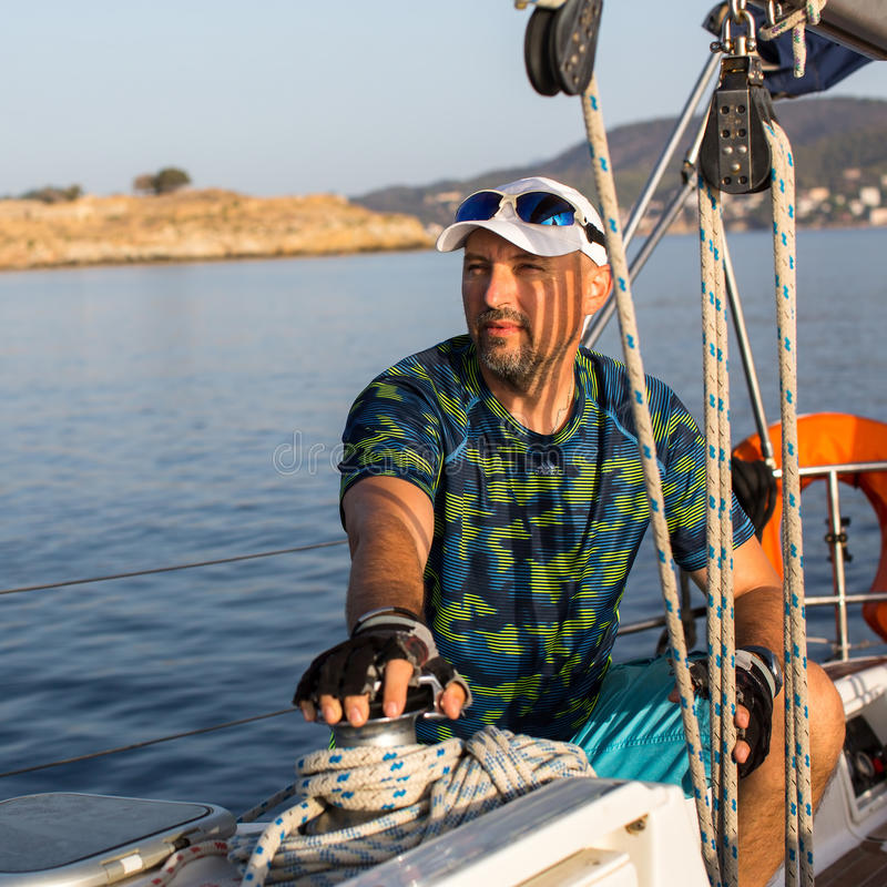 Человек на его яхте Плавать, перемещение стоковые фото