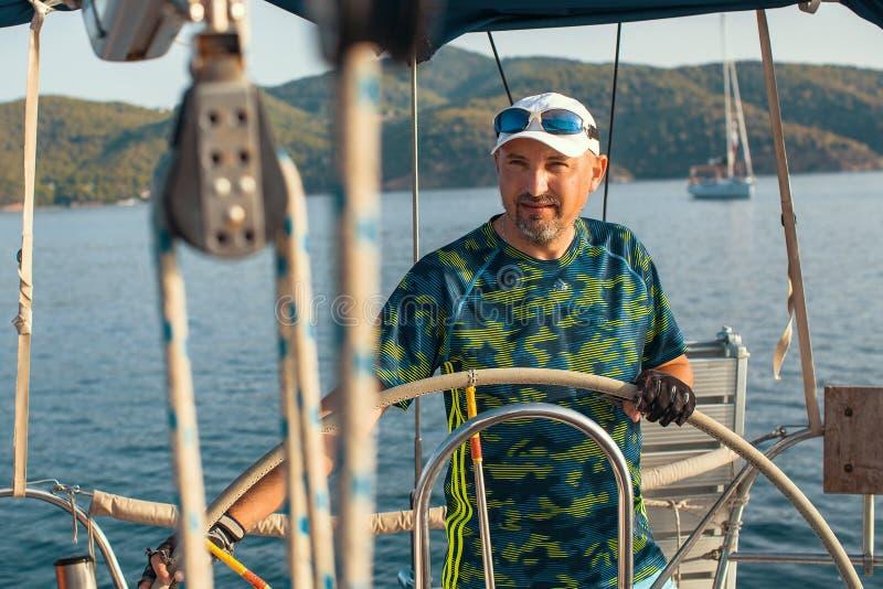 Человек на кормиле водит яхту плавания в море Спорт стоковое фото rf