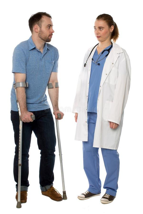 Человек на костылях советуя с с доктором стоковые изображения