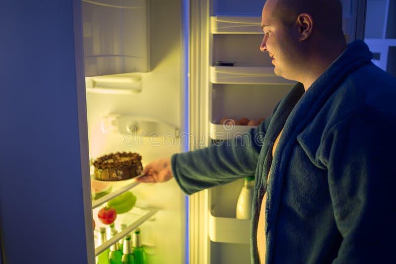 Человек на ноче преступает и принимает весь шоколадный торт от refrige стоковое фото rf