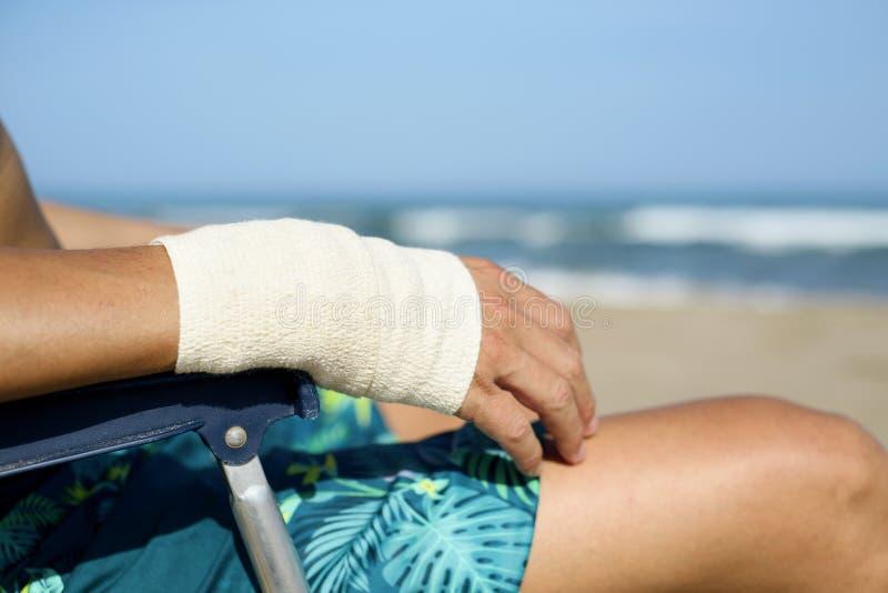 Человек на пляже с повязкой в его запястье руки стоковая фотография rf