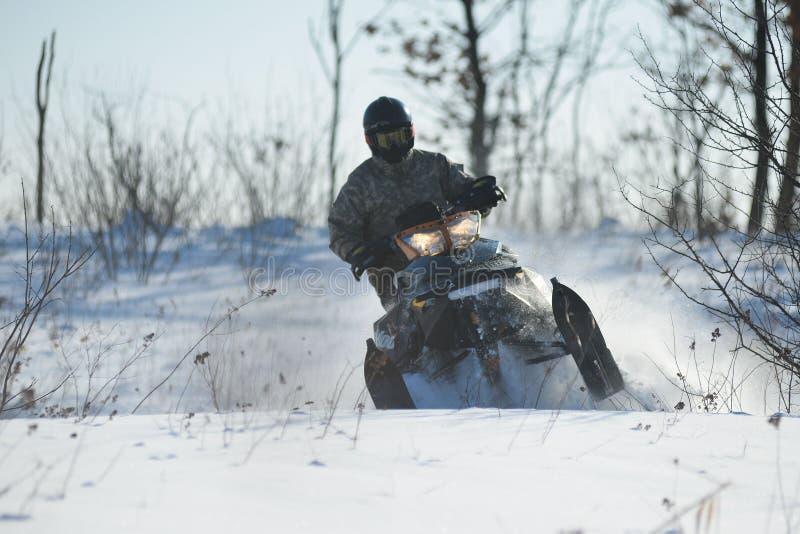 Человек на снегоходе в горе зимы стоковые изображения