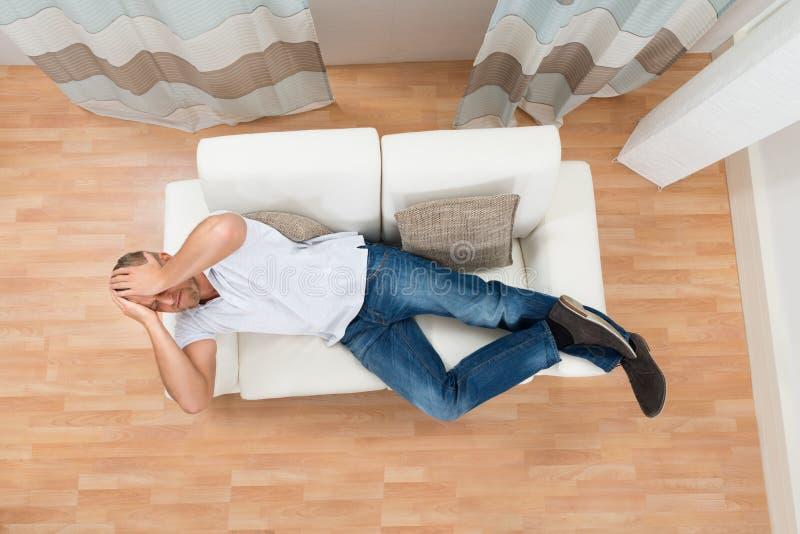 Человек на софе имея головную боль стоковое фото rf