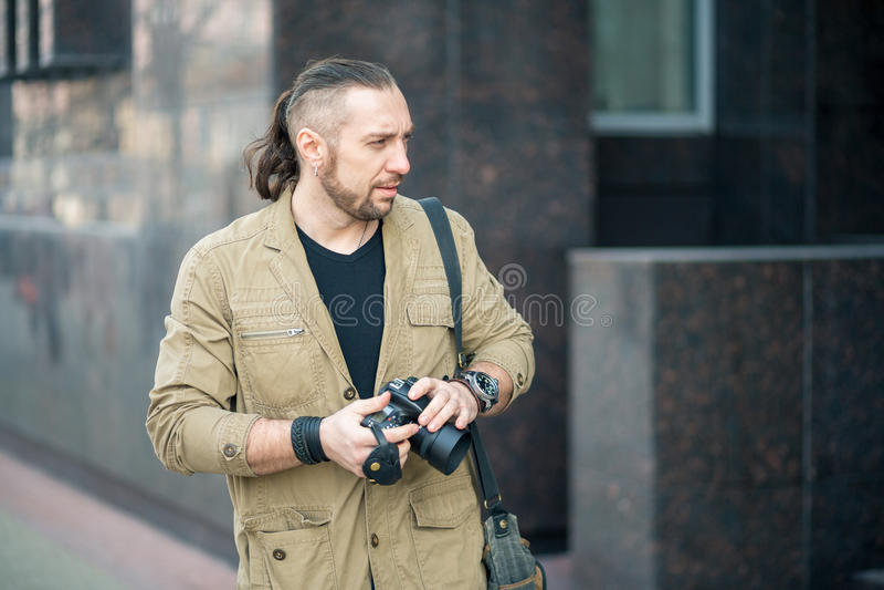 Человек на фотографировать улицы стоковое фото