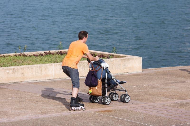 Человек на rollerblades нажимая детскую сидячую коляску стоковые изображения rf