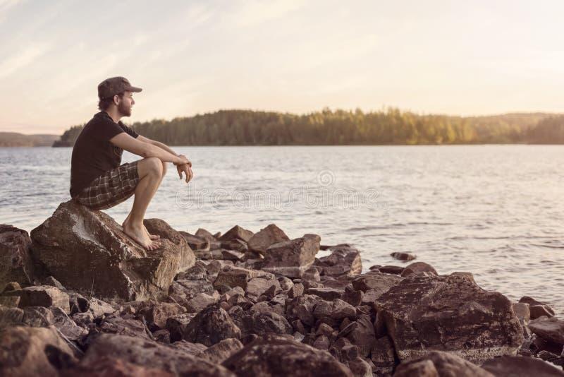 Человек обозревая озеро вскоре после захода солнца стоковое изображение