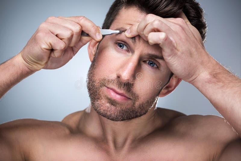 Человек общипывая брови с щипчиками стоковые изображения