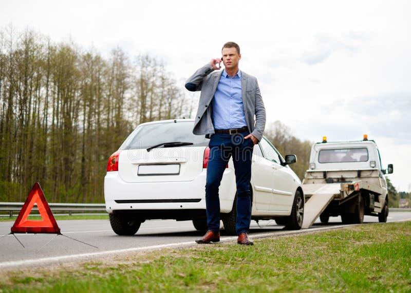 Человек около его сломленного автомобиля на обочине стоковые фото