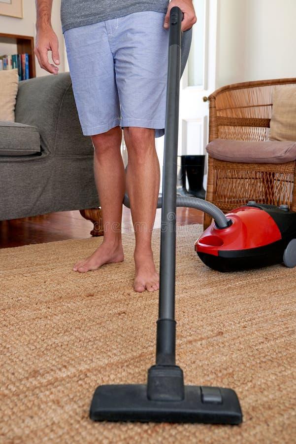 Человек дома вакуумируя ковры стоковое фото rf