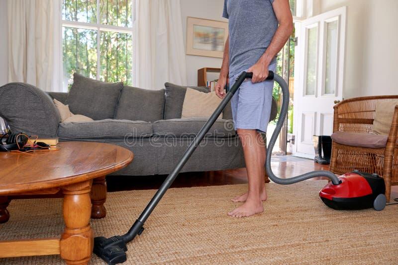 Человек дома вакуумируя ковры стоковая фотография rf