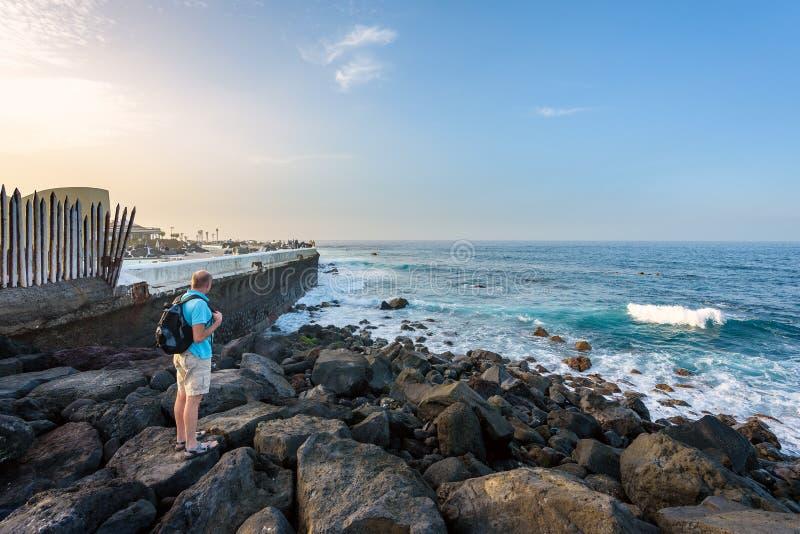 Человек остается на побережье Атлантического океана около городка Puerto de Ла Cruz на острове Тенерифе стоковые фотографии rf