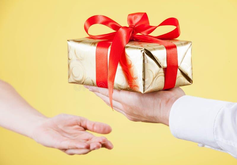 Человек достигая вне подарок к молодой женщине стоковое изображение rf