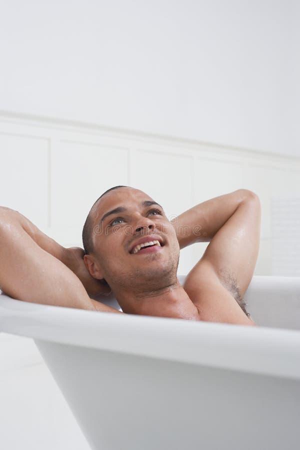 Человек ослабляя в ванне стоковое изображение