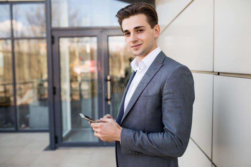 Человек отправляя СМС на телефоне Вскользь городской профессиональный предприниматель используя офисное здание smartphone усмехая стоковая фотография rf