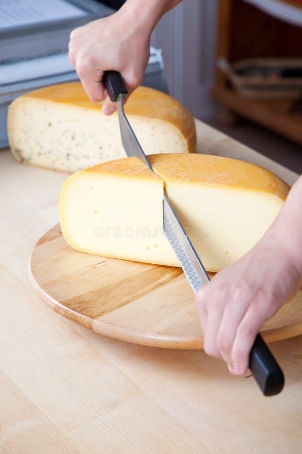 Человек отрезая сыр стоковое фото