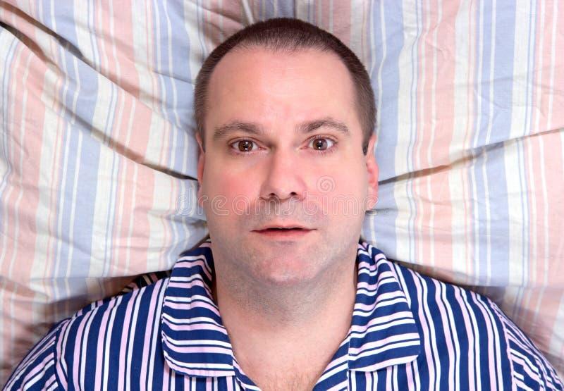 Человек отдыхая в кровати стоковые изображения rf