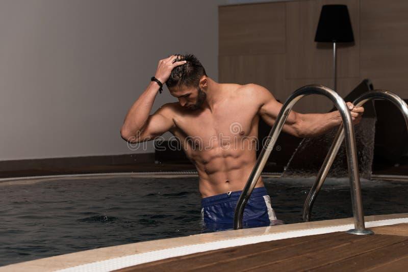Человек отдыхая его оружия на крае бассейна стоковые фото