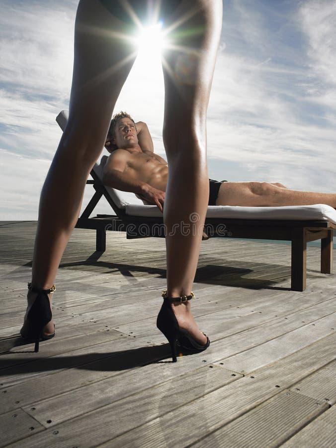 Человек отдыхая на Deckchair и смотря женщину стоковая фотография
