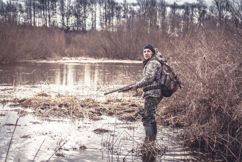Человек охотника проползая в болоте во время сезона звероловства весны стоковая фотография rf