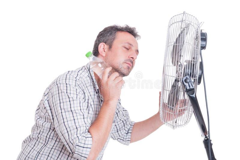 Человек охлаждая вниз перед дуя вентилятором стоковая фотография