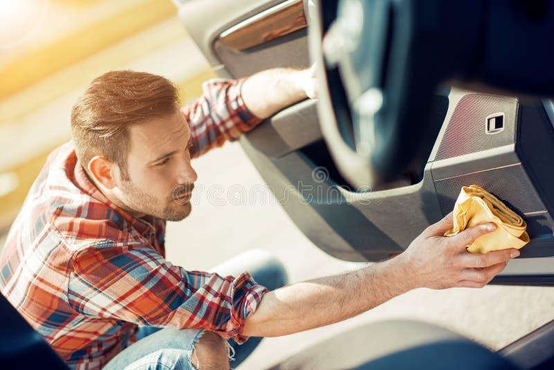 Человек очищая интерьер его автомобиля стоковое изображение