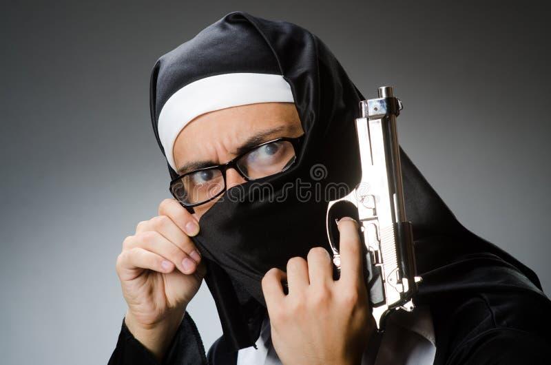 Человек одетый как монашка с личным огнестрельным оружием стоковые изображения