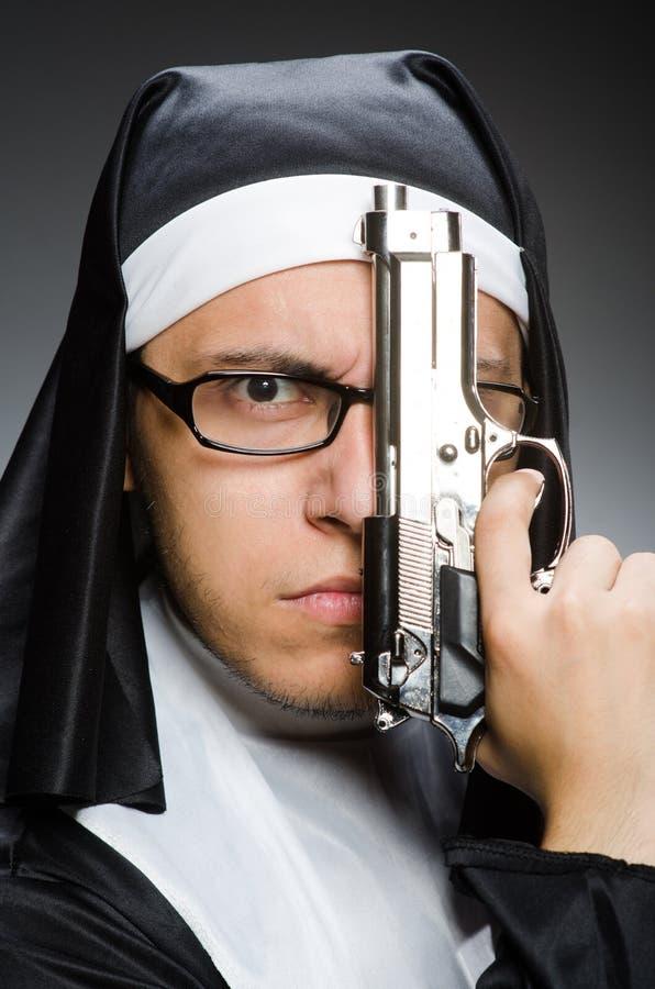 Человек одетый как монашка с личным огнестрельным оружием стоковое изображение rf